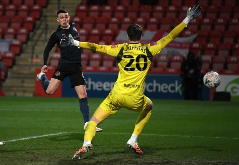 Manchester City midfielder Phil Foden (left) scores against Cheltenham. AFP